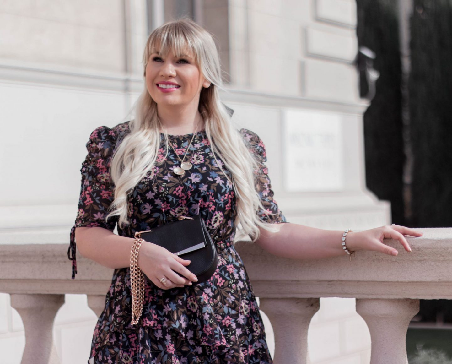 Fashion Blogger Elizabeth Hugen of Lizzie in Lace styles a black floral midi dress with a black saddle bag
