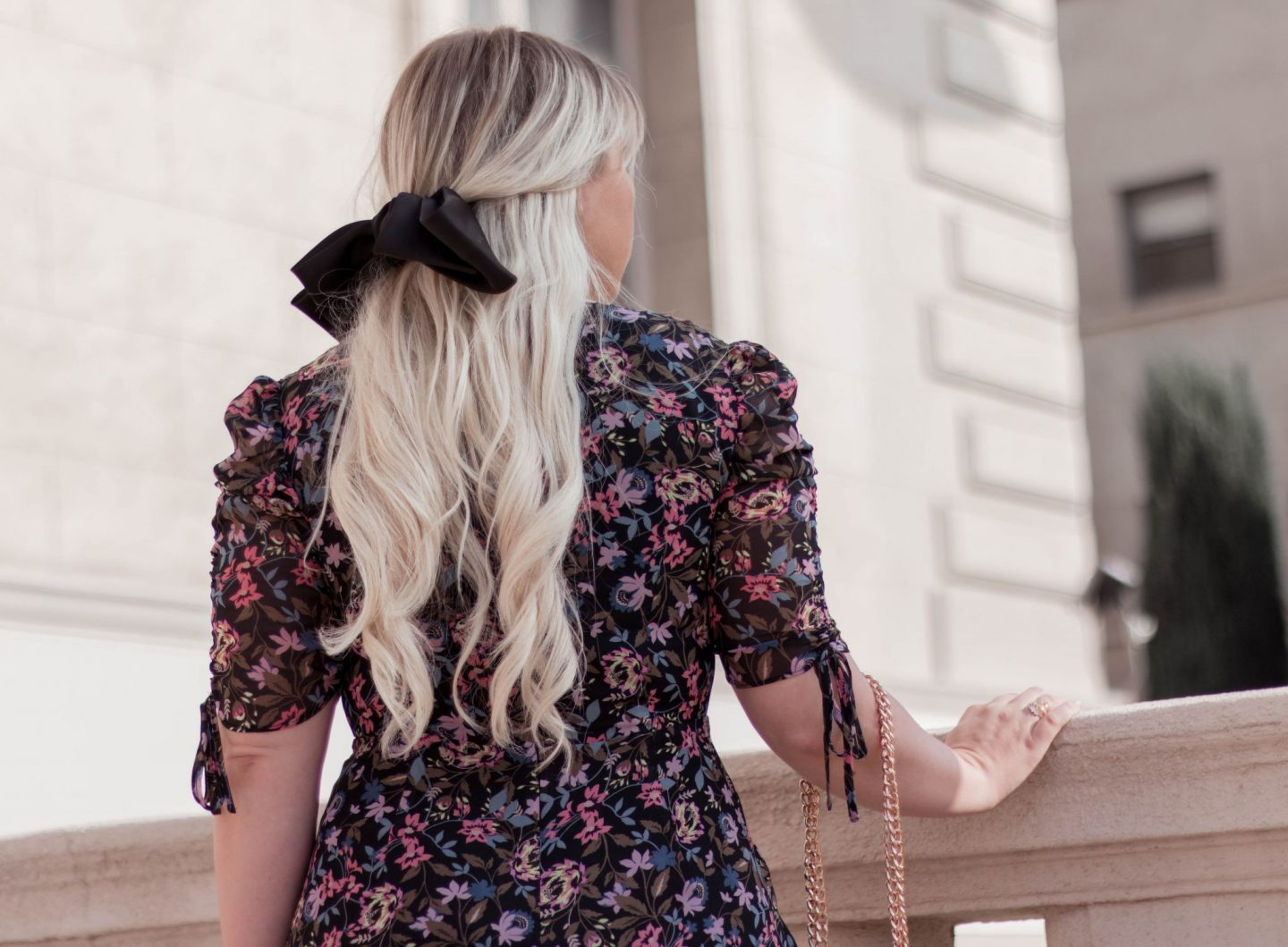 Fashion Blogger Elizabeth Hugen of Lizzie in Lace styles a black floral midi dress with a black oversized hair bow