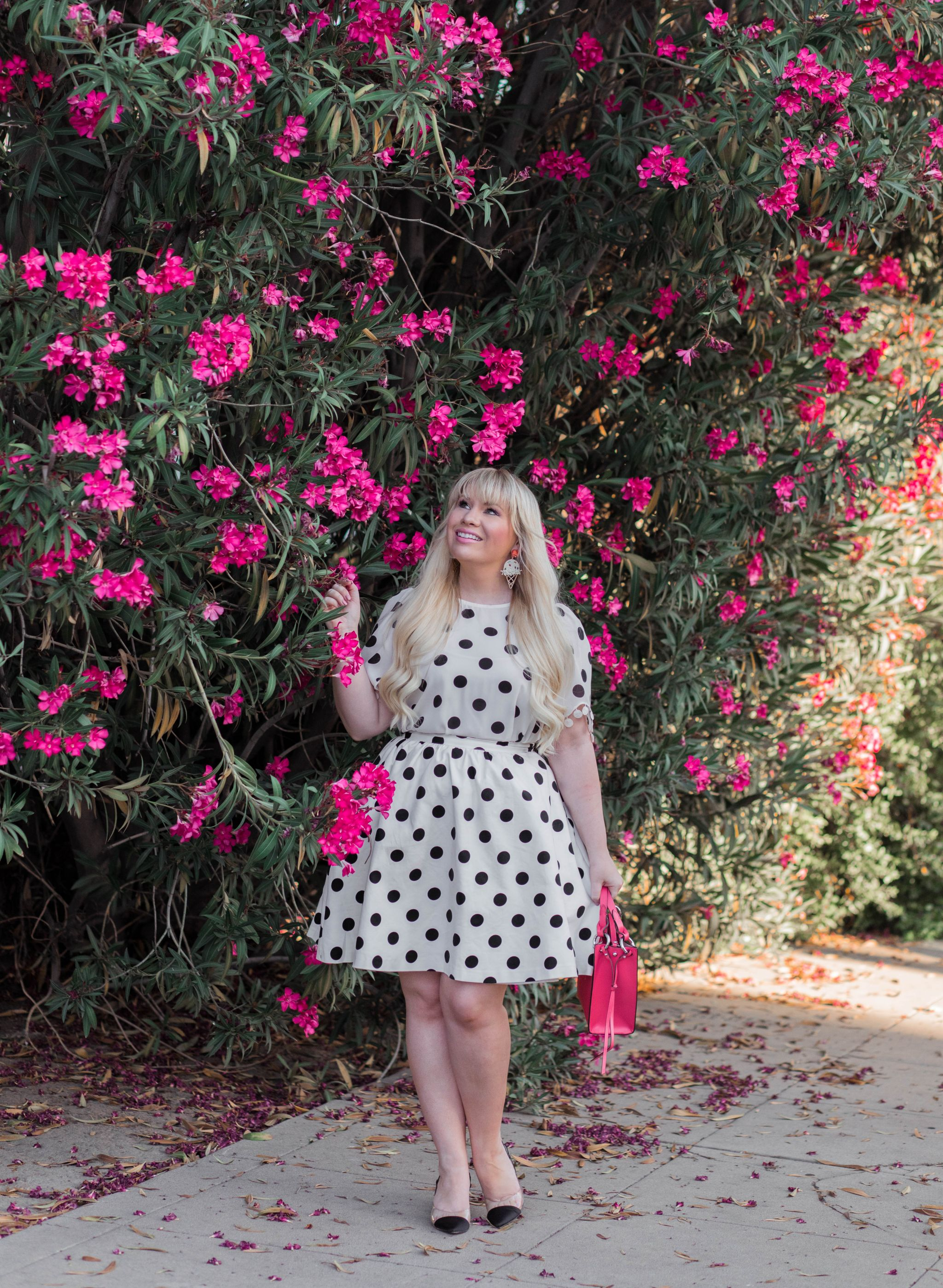 Fashion blogger Elizabeth Hugen wears a black and white polka dress with colorful summer outfit accessories.