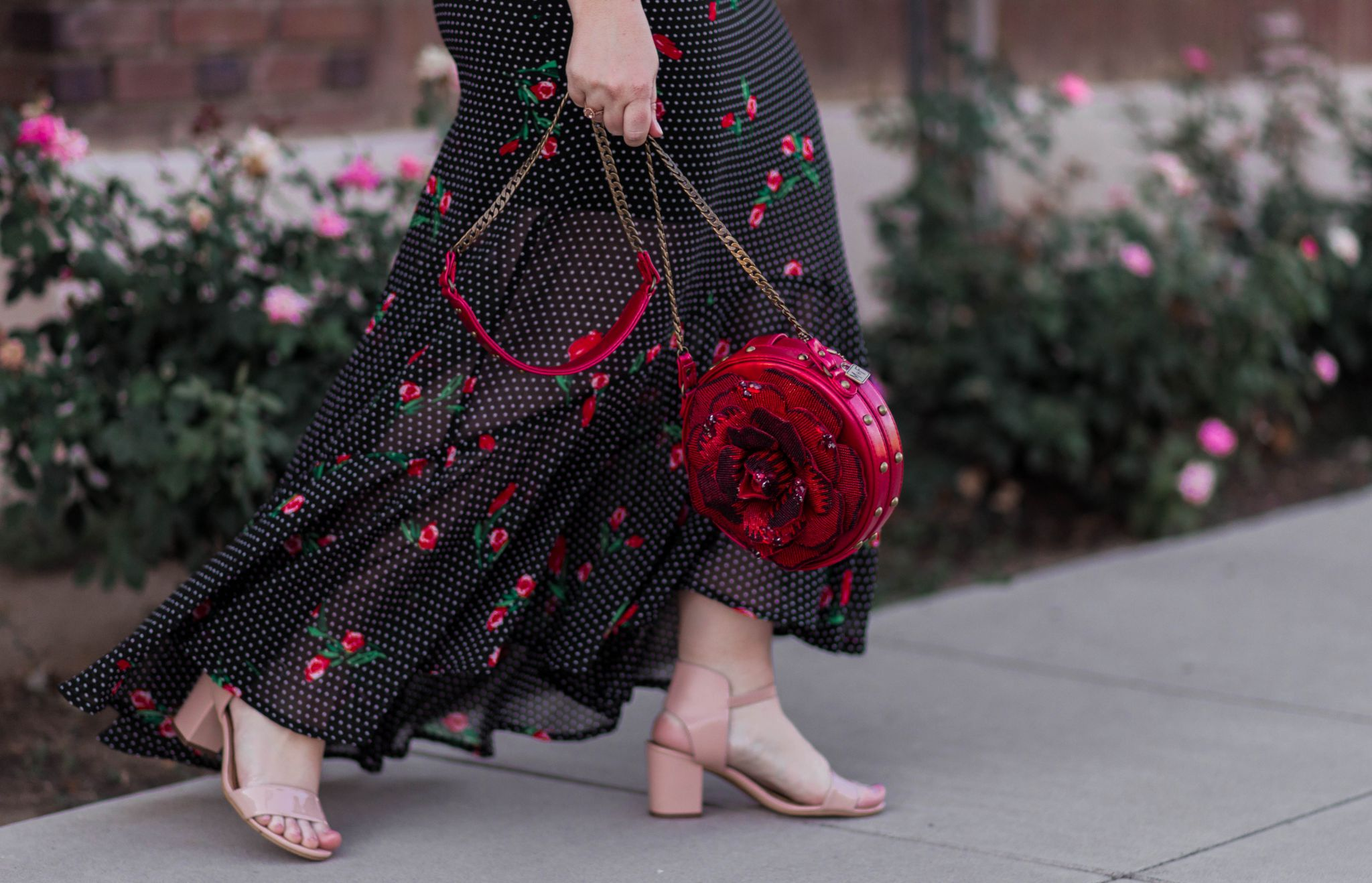 Elizabeth Hugen of Lizzie in Lace styles a beautiful Disney inspired handbag with a black polka dot and rose dress.ess.