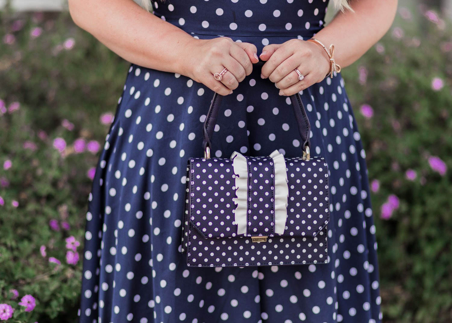 Fashion Blogger Elizabeth Hugen of Lizzie in Lace shares her girly handbag collection including this navy polka dot handbag