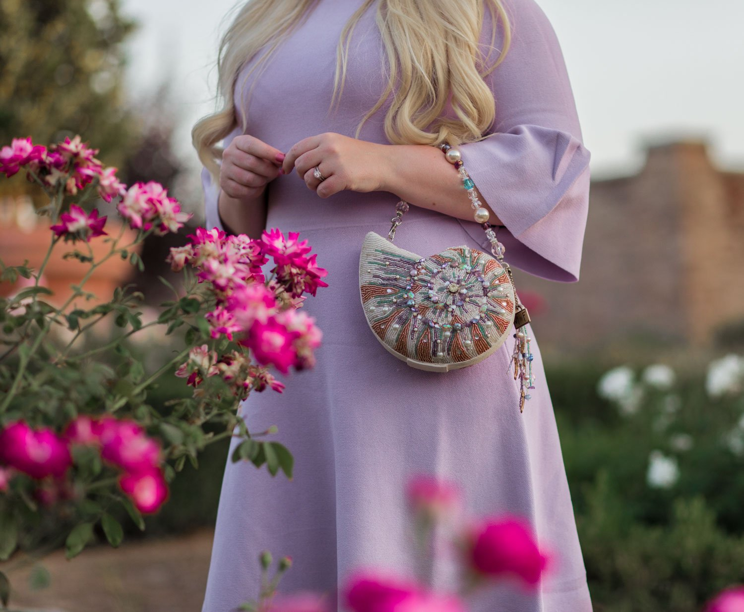 Elizabeth Hugen of Lizzie in Lace wears a lilac Eliza J sweater dress and Mary Frances handbag!