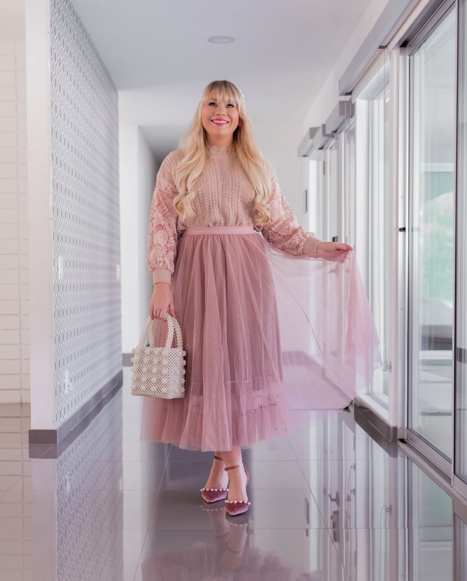 Elizabeth Hugen of Lizzie in Lace wears a pink holiday outfit with a sweater and tulle skirt.