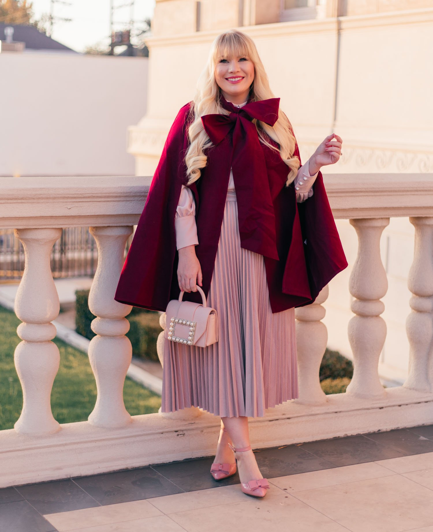 Elizabeth Hugen of Lizzie in Lace shares how to style a cape for fall with this red cape outfit idea!