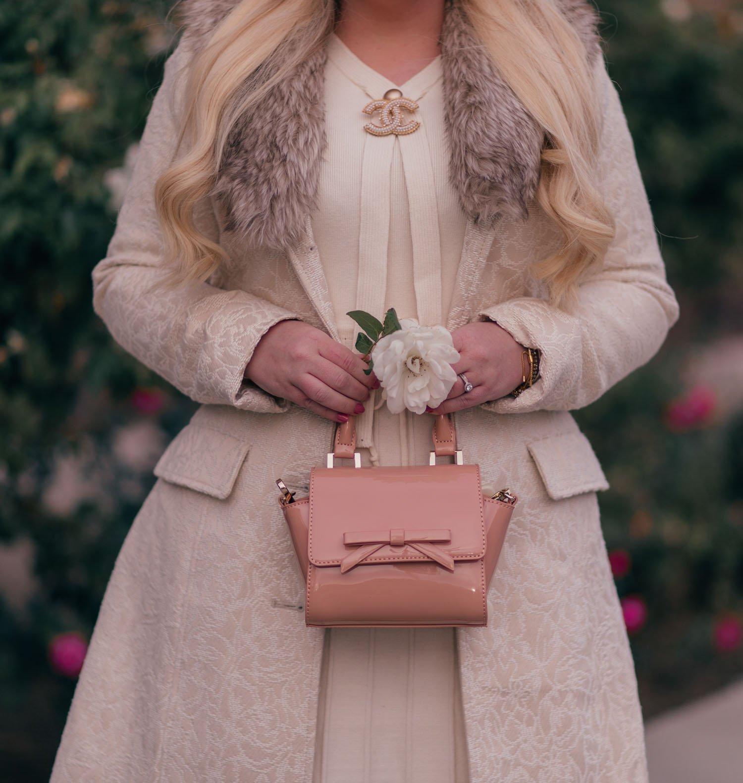Elizabeth Hugen of Lizzie in Lace wears a nude bow handbag.
