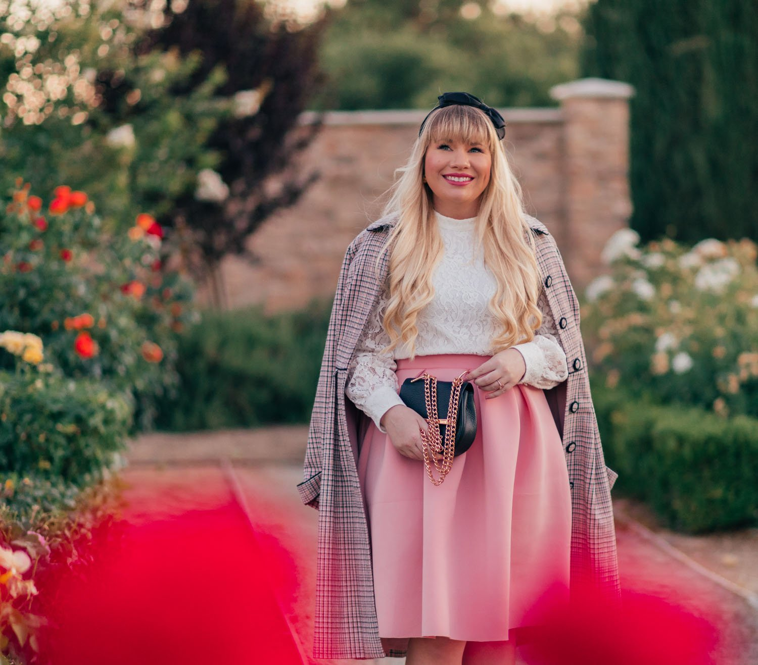 Fashion Blogger Elizabeth Hugen of Lizzie in Lace styles a white lace top with a pink skirt and a plaid pink coat for gossip girl inspired style