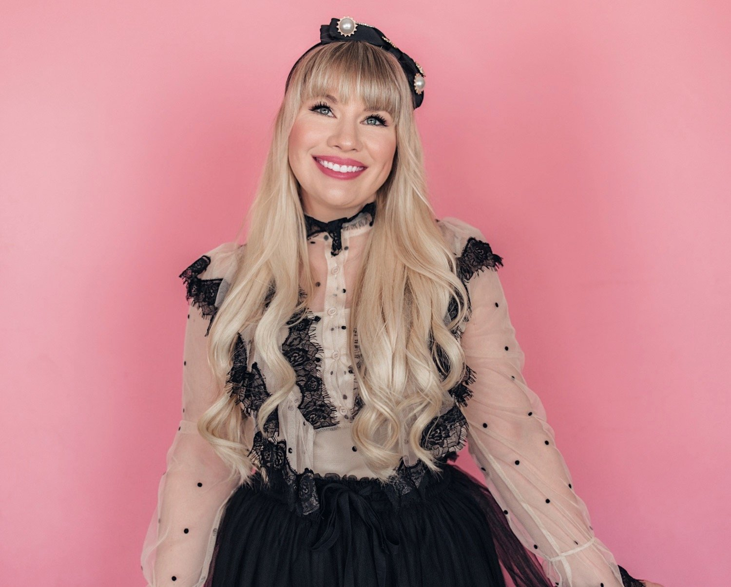 Fashion blogger Elizabeth Hugen of Lizzie in Lace shares a feminine outfit idea with a black polka dot ruffled top and black tulle skirt with black bow headband