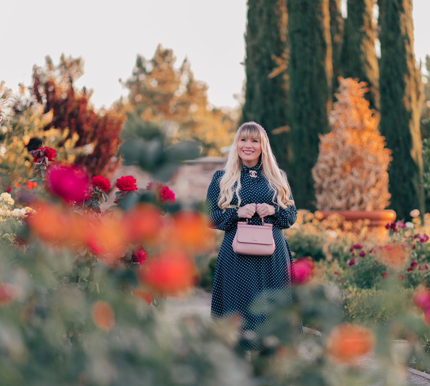 Fashion blogger Elizabeth Hugen of Lizzie in Lace wears a vintage style fall outfit including an emerald green polka dot dress, pearl Chanel brooch and a pink Miss Sicily Dolce and Gabbana handbag