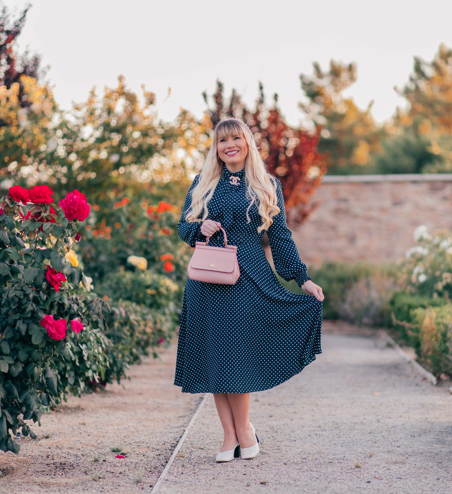 Fashion blogger Elizabeth Hugen of Lizzie in Lace wears a vintage style fall outfit including an emerald green polka dot dress, white everlane heels and a pink Miss Sicily Dolce and Gabbana handbag