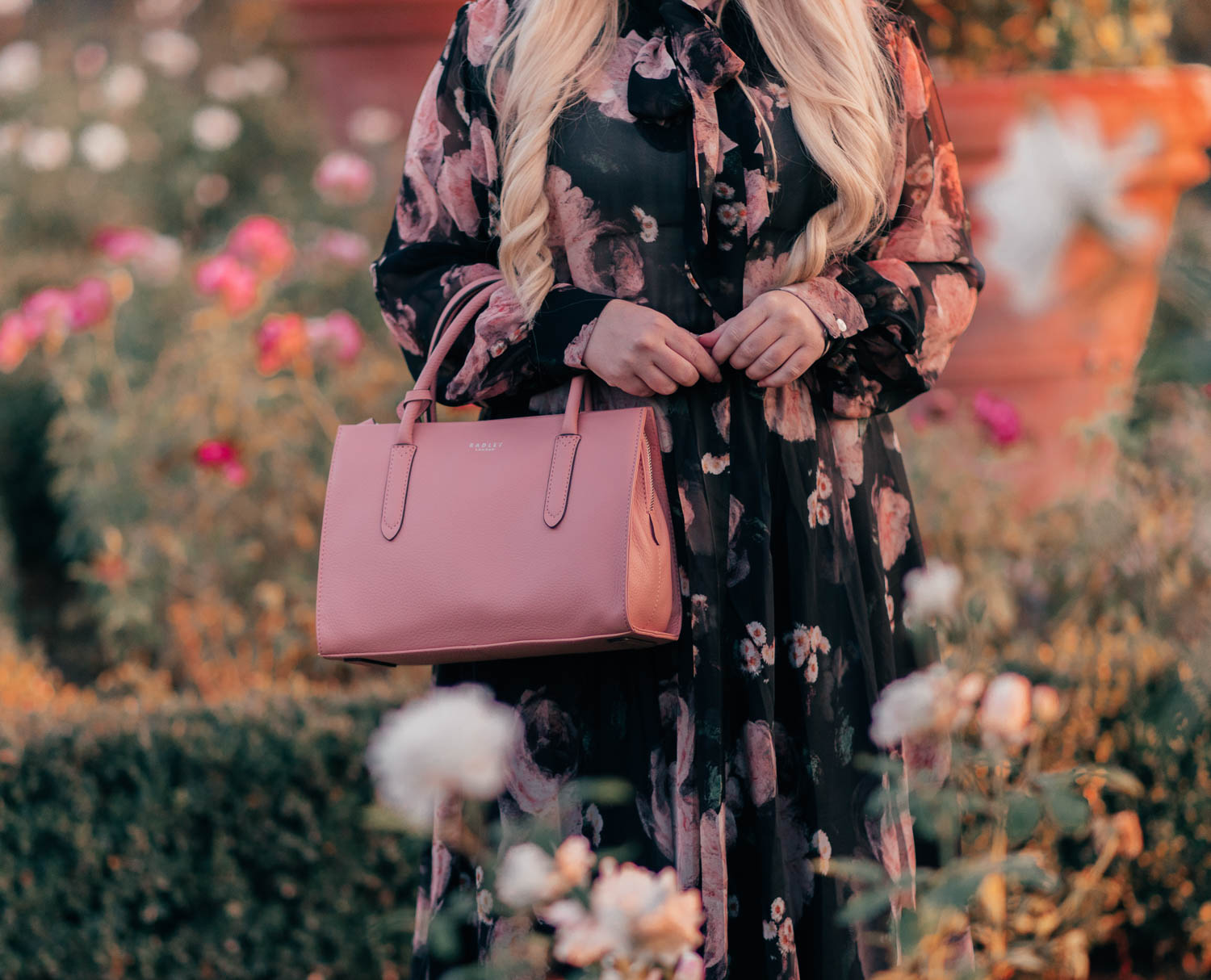 Fashion Blogger Elizabeth Hugen of Lizzie in Lace shares an aesthetic outfit idea with a black floral set and pink handbag for fall