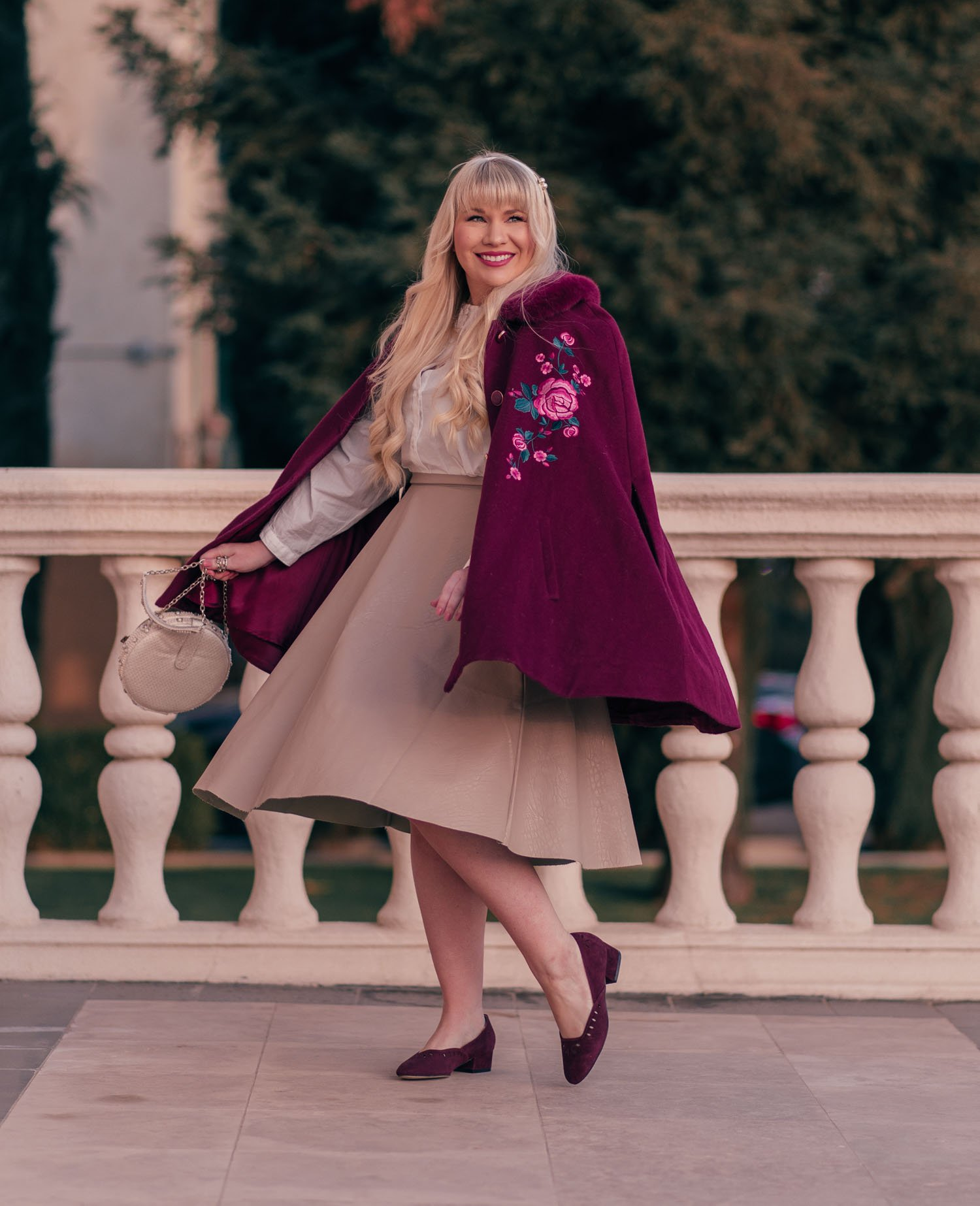 Fashion Blogger Elizabeth Hugen of Lizzie in Lace shares her winter bucket list and a gorgeous red winter cape outfit idea