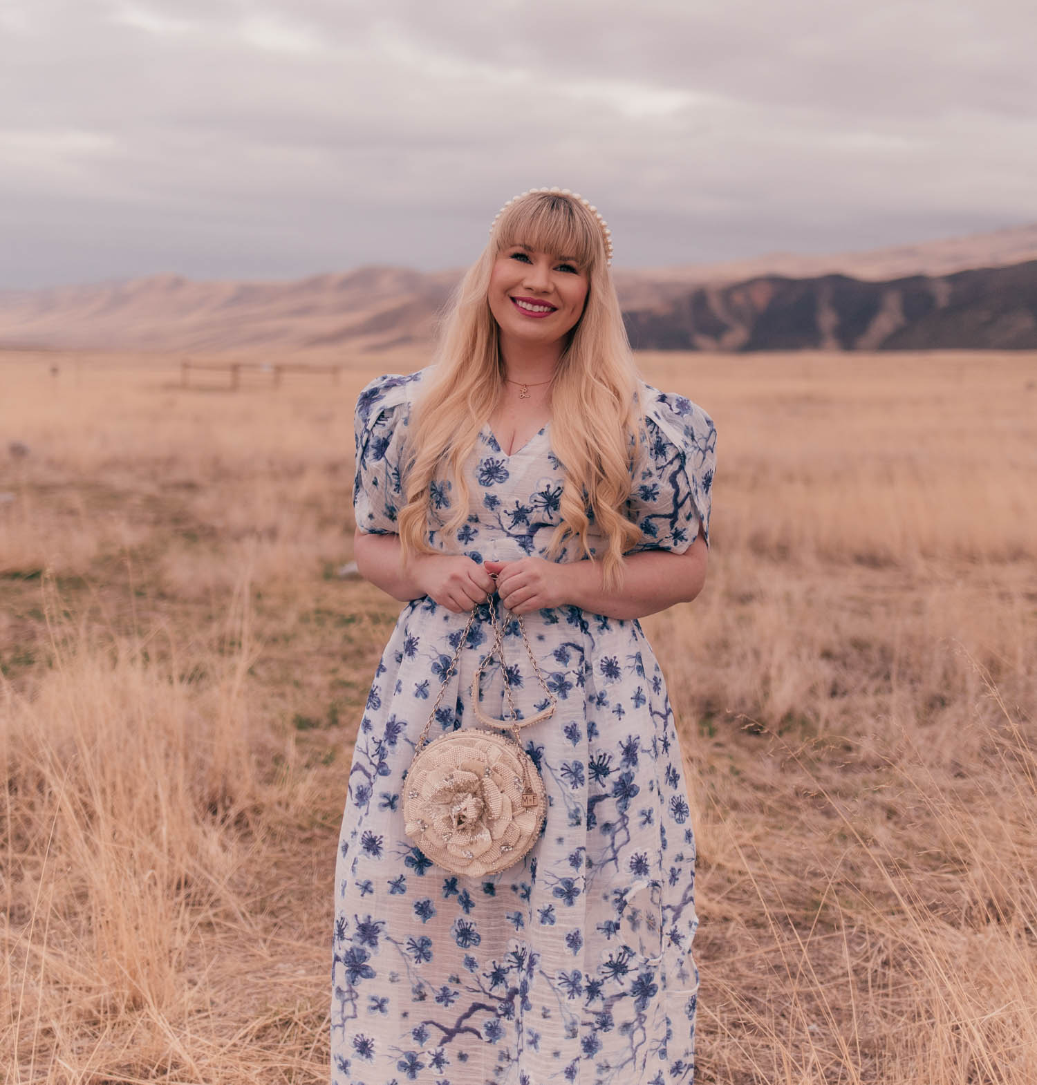 Feminine fashion blogger Elizabeth Hugen of Lizzie in Lace wears a beautiful white and blue floral dress with a Mary Frances handbag for spring and shares an interview with Syra J.