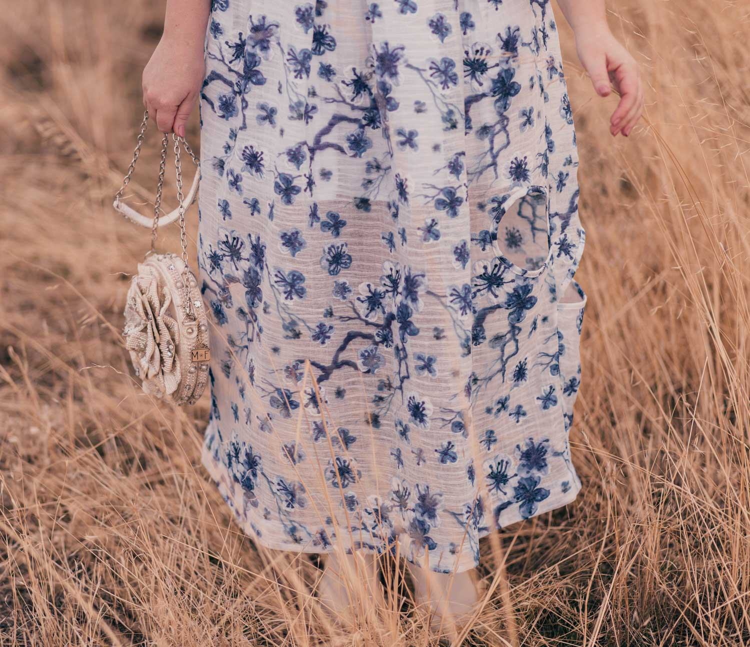 Feminine fashion blogger Elizabeth Hugen of Lizzie in Lace wears a beautiful white and blue floral dress with white boots for spring and shares an interview with Syra J.