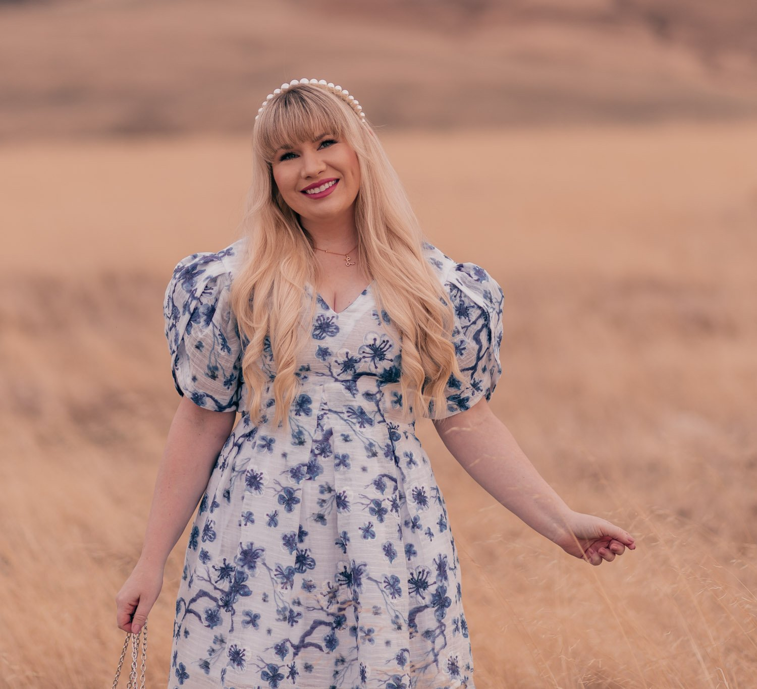 Feminine fashion blogger Elizabeth Hugen of Lizzie in Lace wears a beautiful white and blue floral dress with a Lele Sadoughi pearl headband for spring and shares an interview with Syra J.