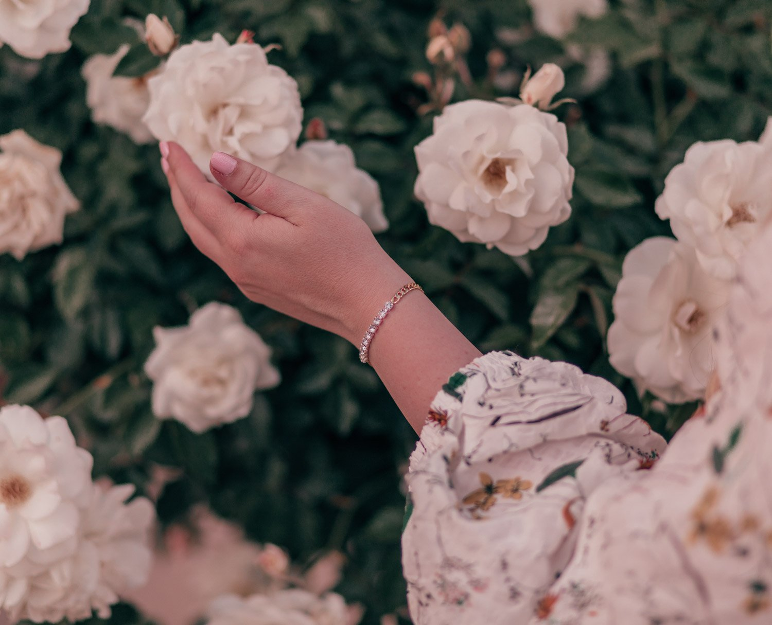 Feminine fashion blogger Elizabeth Hugen of Lizzie in Lace shares her spring 2021 bucket list along with a girly spring outfit idea including this floral Chicwish dress and rhinestone Gorjana bracelet