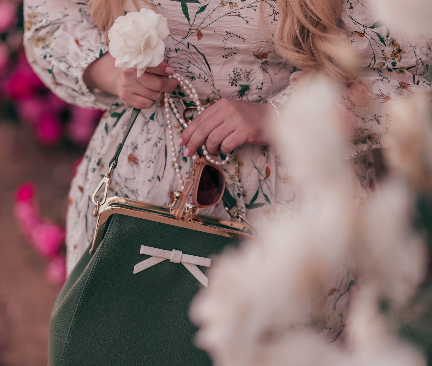 Feminine fashion blogger Elizabeth Hugen of Lizzie in Lace shares her spring 2021 bucket list along with a girly spring outfit idea including this floral Chicwish dress and blush Sunski sunglasses with pearl sunglasses chain