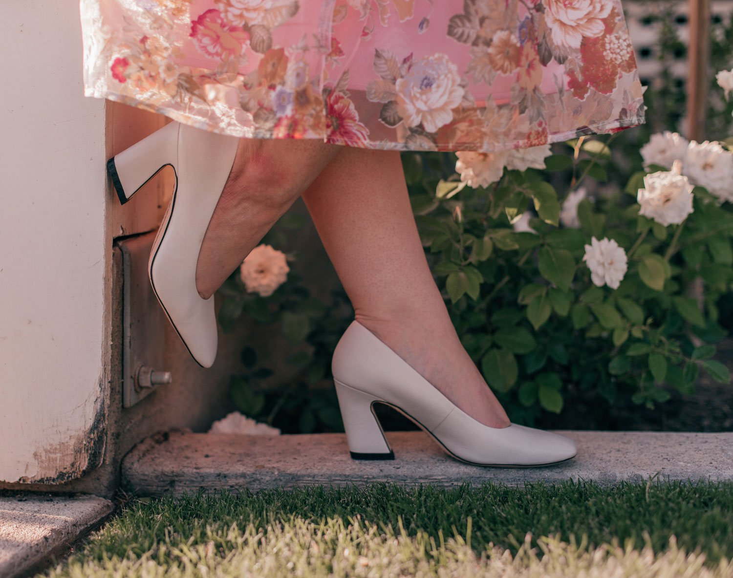 Feminine Fashion Blogger Elizabeth Hugen of Lizzie in Lace shares a feminine floral summer outfit idea including a white lace top, pink floral chicwish skirt and white franco sarto heels
