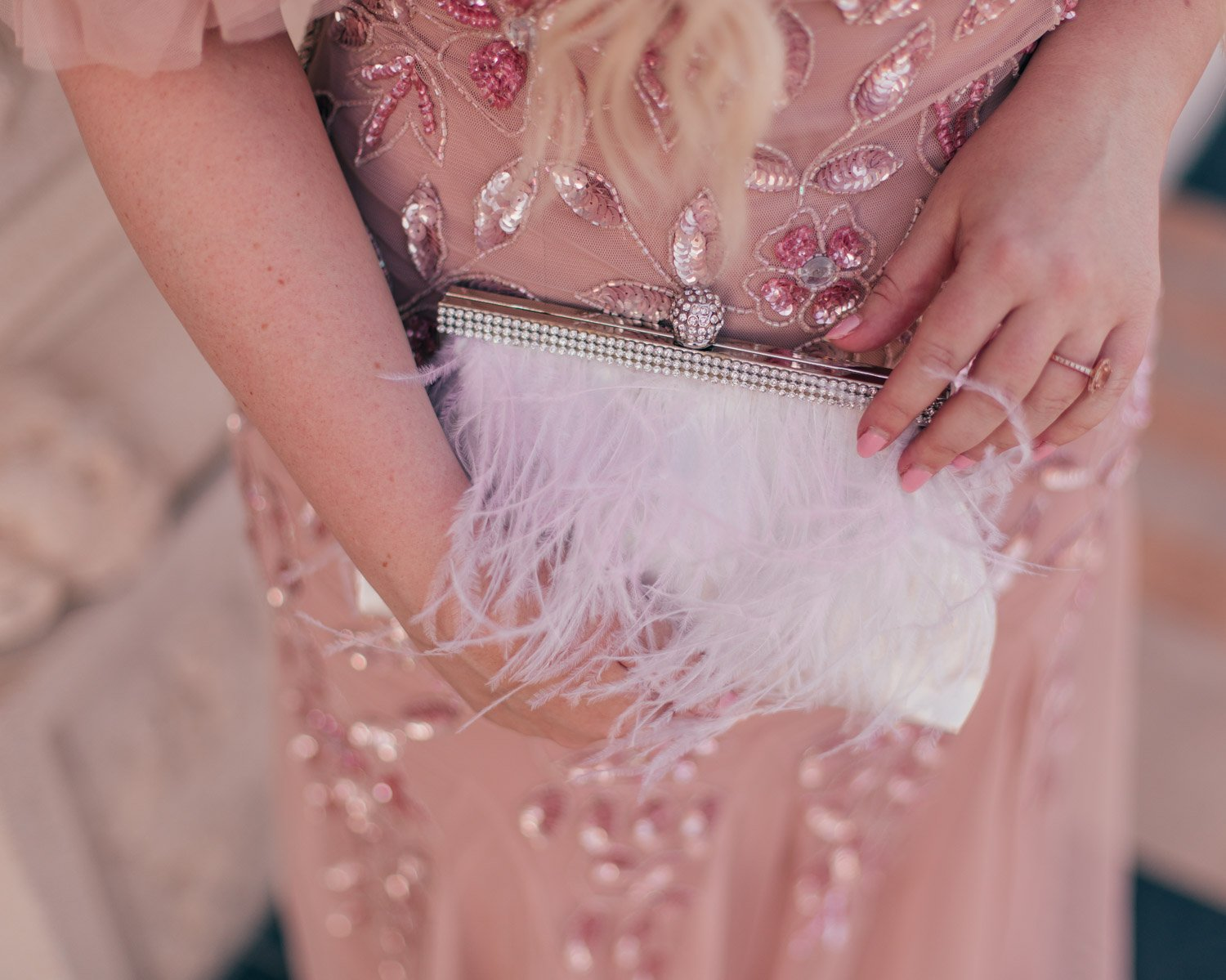 Feminine Fashion Blogger Elizabeth Hugen of Lizzie in Lace shares her favorite Summer Wedding Guest Dresses including a white feather clutch