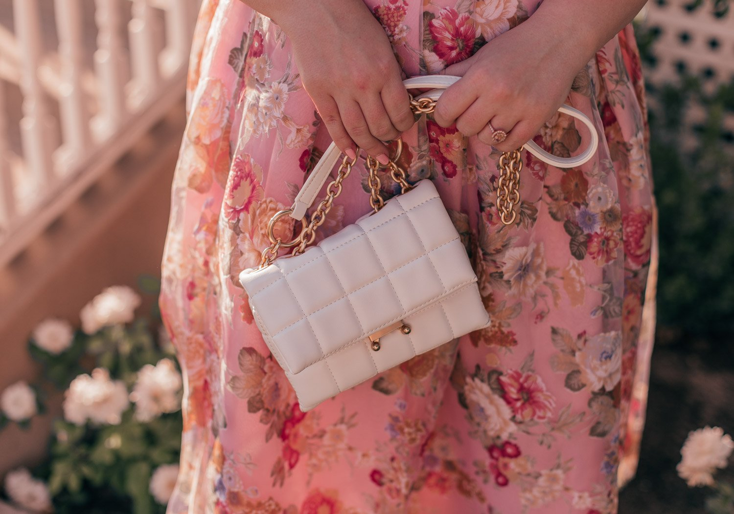 Feminine Fashion Blogger Elizabeth Hugen of Lizzie in Lace shares a feminine floral summer outfit idea including a white lace top, pink floral chicwish skirt and white house of want bag