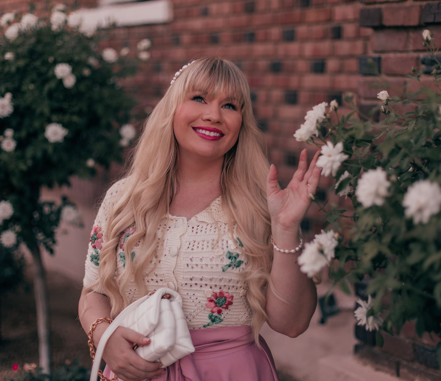 Feminine fashion blogger Elizabeth Hugen of Lizzie in lace shares How to Wear a Vintage Inspired Cardigan for Summer including a white quilted handbag