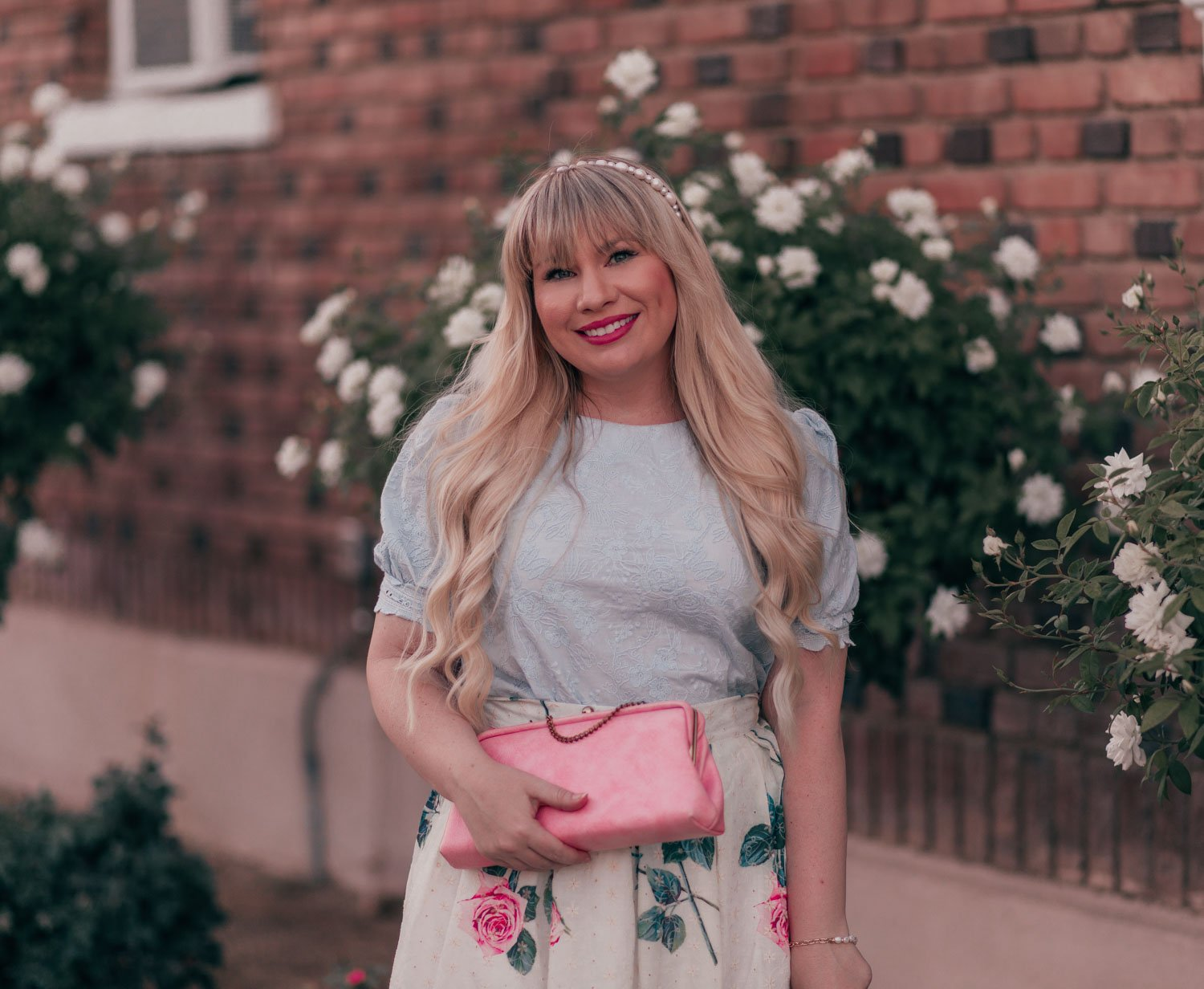 Feminine fashion blogger Elizabeth Hugen of Lizzie in Lace shares a pretty pastel vintage inspired floral skirt outfit with a light blue puff sleeve top and pink vintage handbag