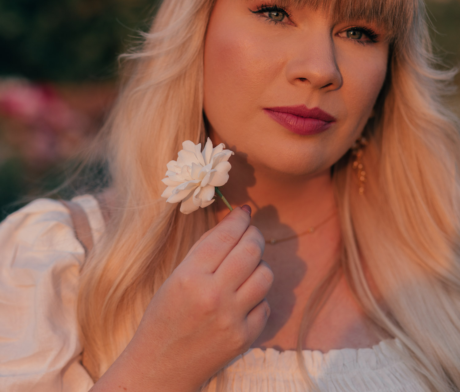 Feminine Fashion Blogger Elizabeth Hugen of Lizzie in Lace shares a cottagecore outfit idea including this white puff sleeve dress from Chicwish, dainty gold jewelry and feminine makeup look