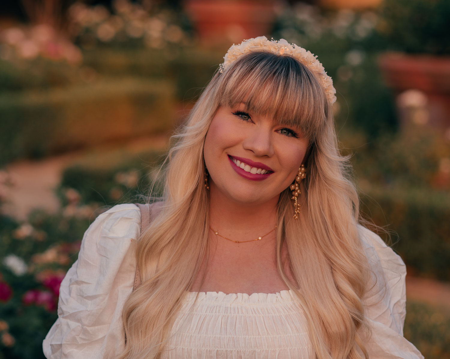 Feminine Fashion Blogger Elizabeth Hugen of Lizzie in Lace shares a cottagecore outfit idea including this white puff sleeve dress from Chicwish, dainty gold jewelry and floral headband
