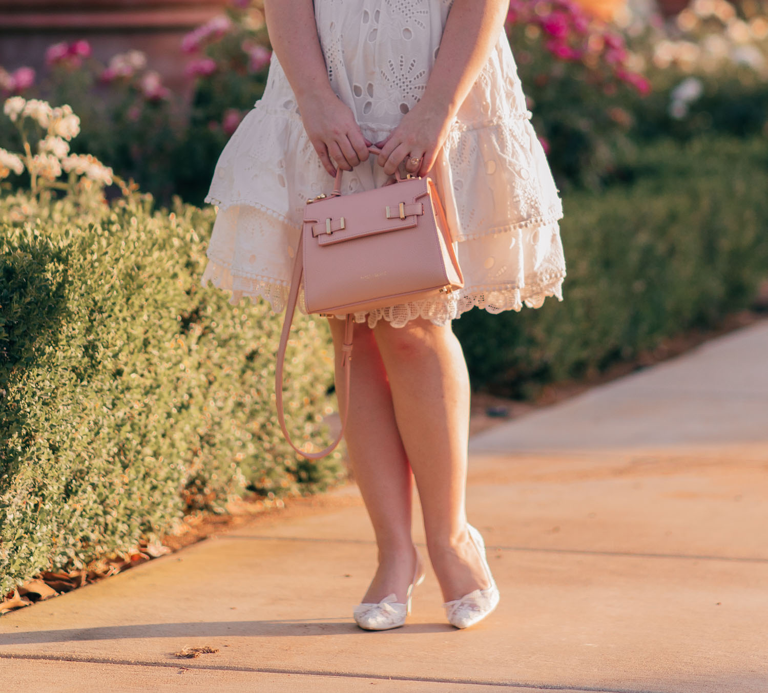 Feminine Fashion Blogger Elizabeth Hugen of Lizzie in Lace shares the perfect white summer dress from Chicwish and pink Teddy Blake handbag
