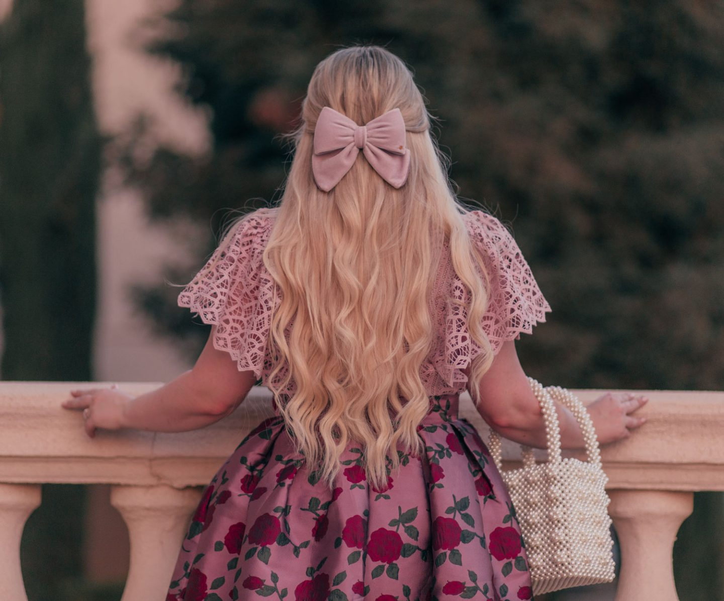 Feminine Fashion Blogger Elizabeth Hugen of Lizzie in Lace shares 5 Easy Ways to Dress More Feminine and wear a pink outfit with a lace top, velvet hair bow and floral skirt