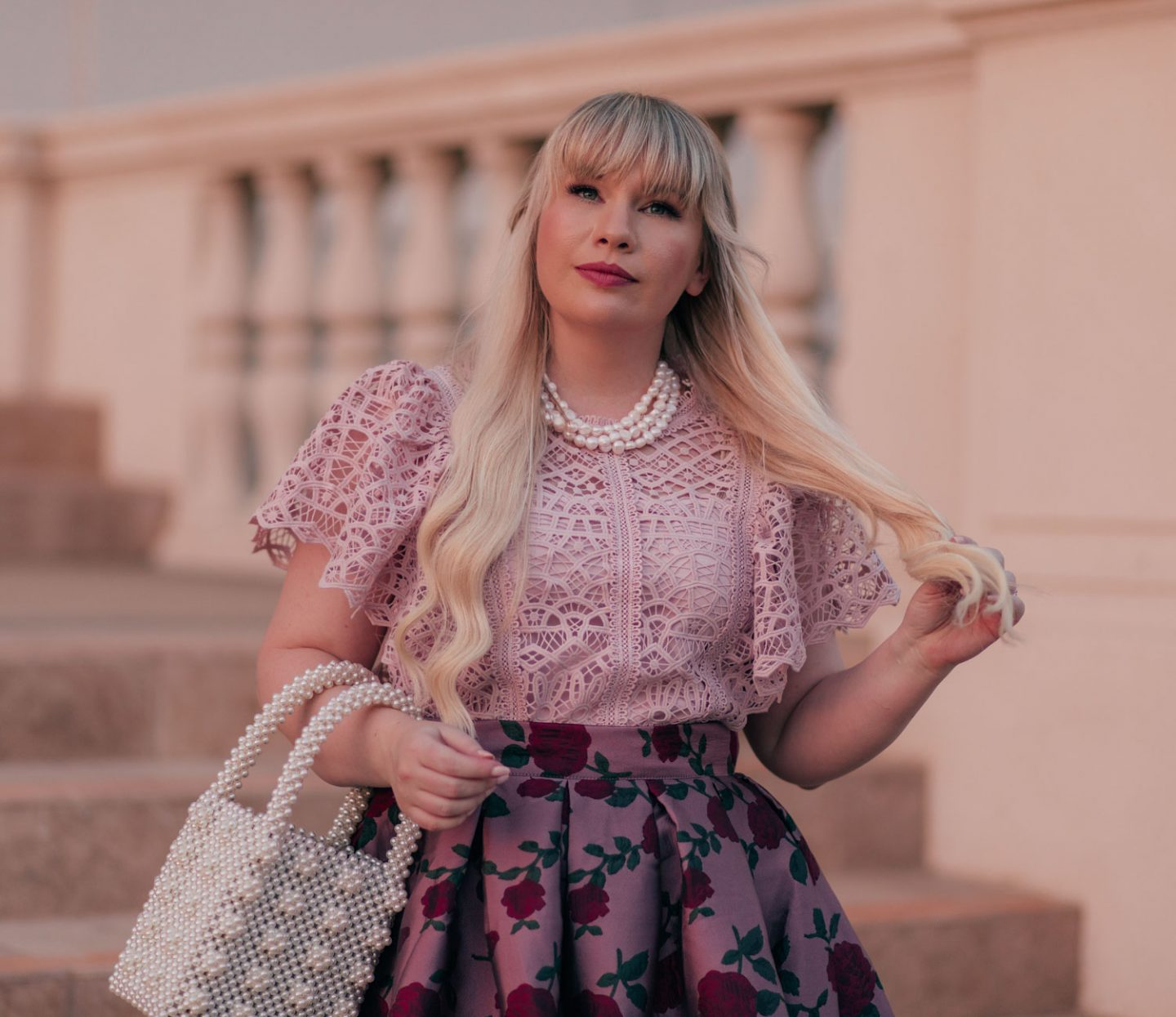 Feminine Fashion Blogger Elizabeth Hugen of Lizzie in Lace shares 5 Easy Ways to Dress More Feminine and wear a pink outfit with a lace top, pearl necklace and floral skirt
