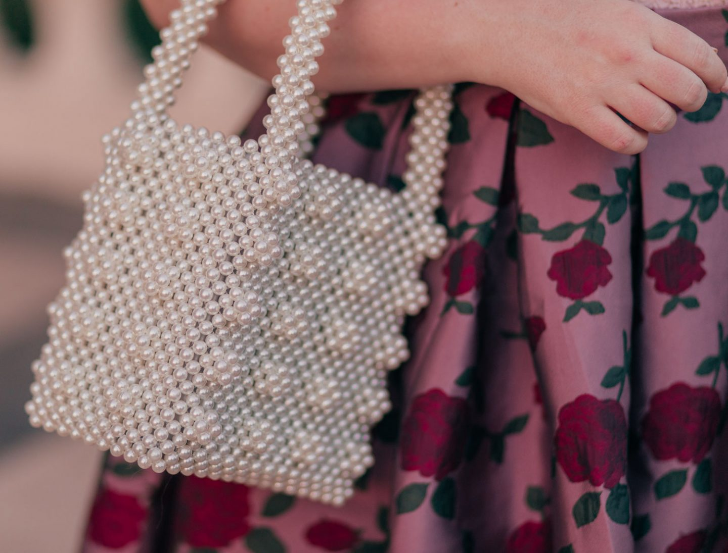 Feminine Fashion Blogger Elizabeth Hugen of Lizzie in Lace shares 5 Easy Ways to Dress More Feminine and wear a pink outfit with a pearl handbag and floral skirt